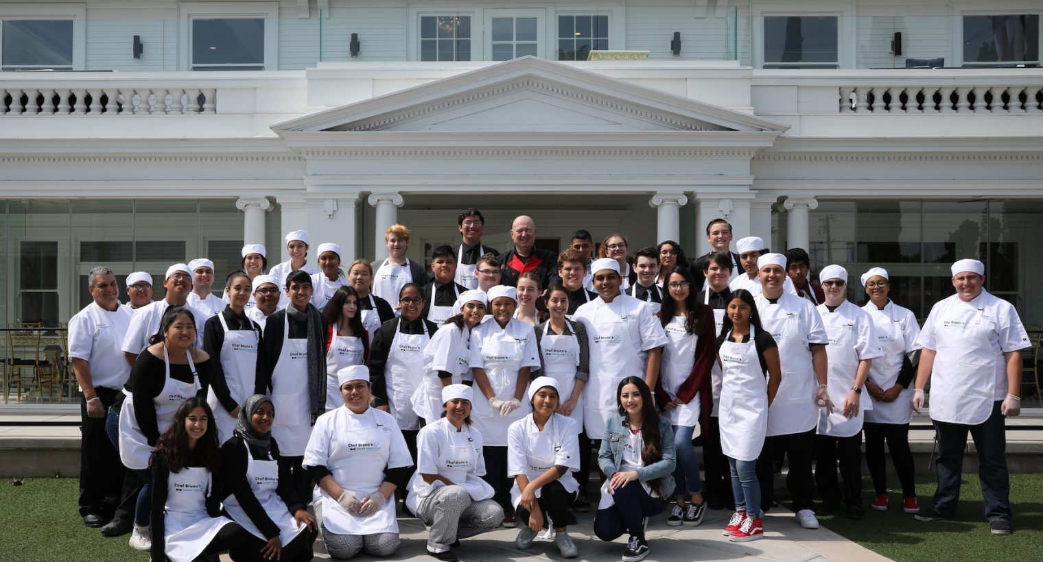 bruno serato with 2019 hospitality academy students in front of anaheim white house