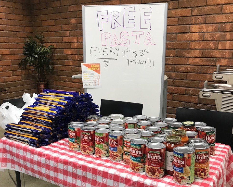 free pasta whiteboard sign behind pasta and cans of hunts pasta sauce on red checkered table